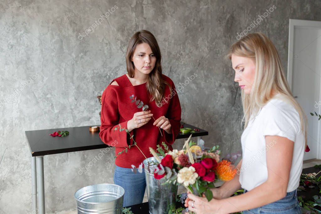 Florist workplace. Woman arranging a bouquet with roses, chrysanthemum, carnation and other flowers. A teacher and student of floristry in master classes or courses
