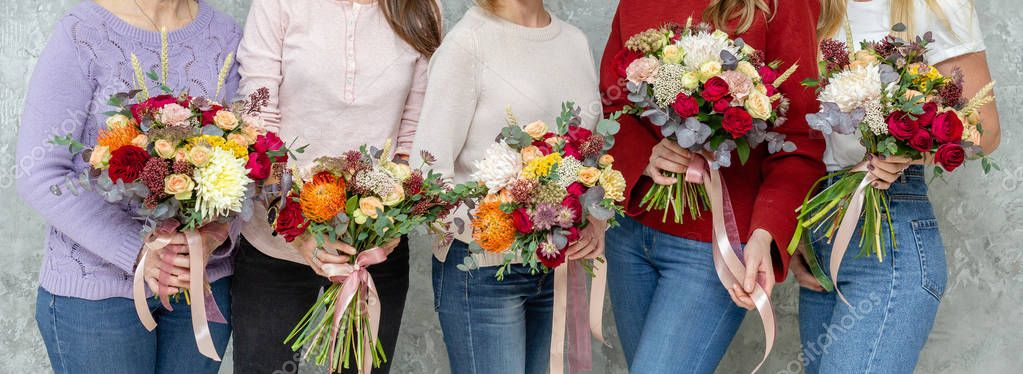 Florist workplace. Woman arranging a bouquet with roses, chrysanthemum, carnation and other flowers. A teacher and students of floristry in master classes or courses