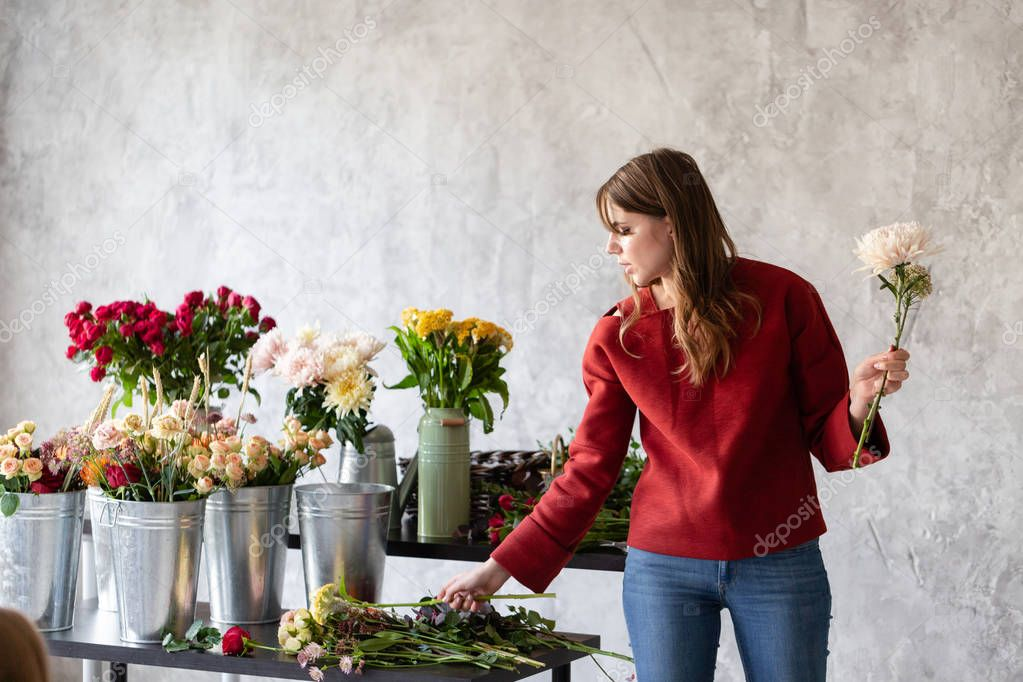 Florist workplace. Woman arranging a bouquet with roses, chrysanthemum, carnation and other flowers. A teacher of floristry in master classes or courses