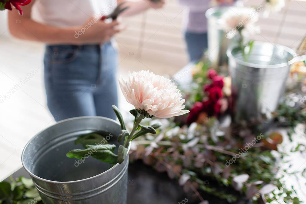 Close-up flowers in a metal bucket. Florist workplace. Woman arranging a bouquet with roses, chrysanthemum, carnation and other flowers. A teacher of floristry in master classes or courses