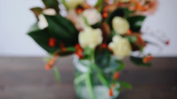 Closeup floral arrangement. Flowers in a glass vase. Woman picking fresh flowers to create beautiful bouquet in vase. Flower shop concept