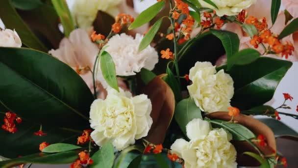 Closeup aranžmá. Květiny ve skleněné váze. Žena trhá čerstvé květiny, vytvořit krásnou kytici ve váze. Flower shop koncept