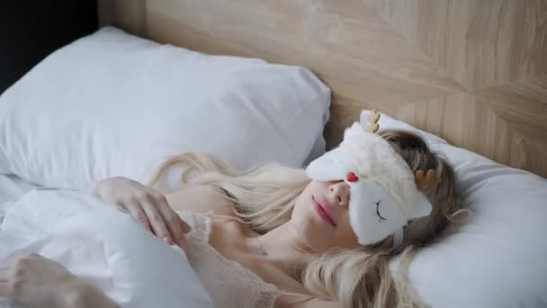 Young woman sleep on comfortable bed in a mask for sleeping. Blindfold on eye. Morning in hotel room. White pillow and blanket