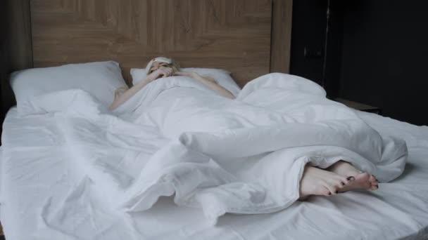 Mladá žena spí na pohodlné posteli v masce na spaní. Zavázané oči. Dobré ráno v hotelovém pokoji. Bílý polštář a přikrývka