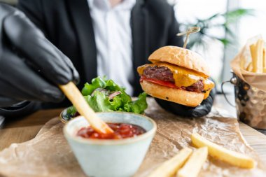 Young man in business suit and black gloves eating delicious juicy cheeseburger with beef chop. Burgers in the cafe with salad and fries, fast food.