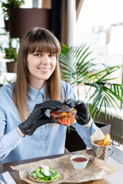 Young woman in blue shirt and black gloves eating delicious juicy hamburger with beef chop. Burgers in the cafe with salad and fries, girl eating fast food.