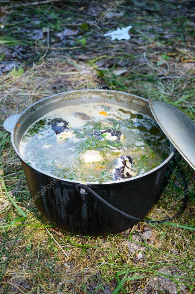 Fish soup boils in cauldron at the stake on the nature. Soup in a pot in the fire.  Close-up.