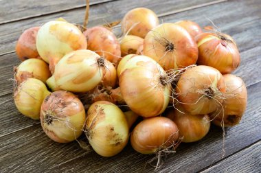 A large bunch of onions on a wooden table. Fresh harvest, popular healthy vegetables.