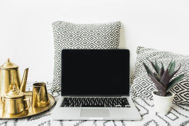 Stylish front view home office desk workspace with blank screen laptop, golden teapot on tray and succulent. Lifestyle blog hero header. Creative blog or social media background. Mock up template.