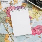 Cestovní poznámky mock nahoru s papírem prázdné. Mapa Evropy, fotoaparát, sluneční brýle a poznámkového bloku. Plochá ležel, horní pohled