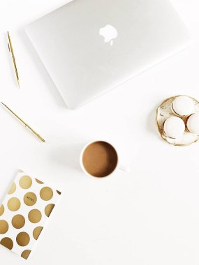 Modern gold stylized home office desk with laptop, macaroons, pen, coffee mug on white background. Flat lay, top view lifestyle concept.