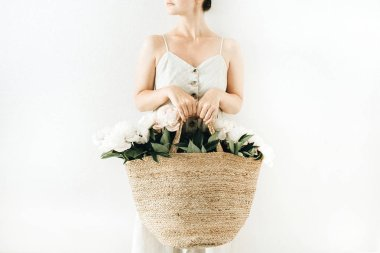 Young pretty woman holding straw bag with white peony flowers on white background. Fashion concept.