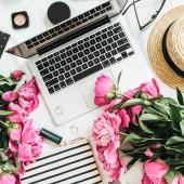 Lapos laikus divat Női íróasztal, laptop, rózsaszín bazsarózsa virágok, kozmetikai kellékek. Felülnézet csendélet blogger háttér.