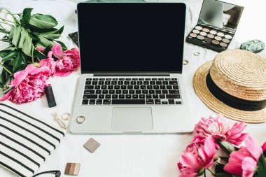 Flat lay, top view female office desk workspace mock up with laptop, pink peony flowers bouquet, accessories and cosmetics. Fashion, beauty or lifestyle blog concept.