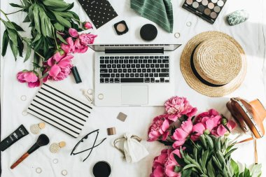 Flat lay, top view women fashion office desk workspace with peony flowers, laptop, cosmetics, accessories on white background.