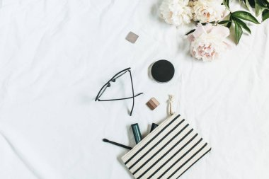 Flat lay, top view fashion background with peony flowers, glasses, cosmetics. Beauty or fashion blog concept.