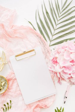 Modern home office desk workspace with blank paper clipboard, pink hydrangea flowers bouquet, tropical palm leaf, pastel blanket, monstera leaf plate and accessories on white background. Flat lay, top view rose gold mockup.