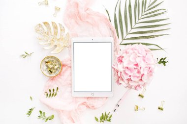 Blank screen tablet, pink hydrangea flowers bouquet, tropical palm leaf, pastel blanket, monstera leaf plate and accessories on white background. Flat lay, top view rose gold home office desk workspace mockup.