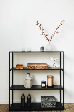 Modern nordic interior design concept. Stylish black rack with caskets, cotton branch, vase, candles and bird figurine at white wall. Interior blog lifestyle composition.