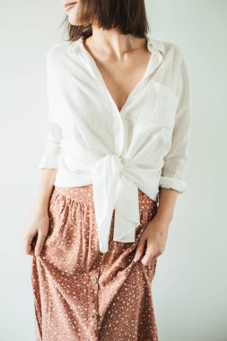 Young pretty woman in long skirt, white blouse on white background. Fashion lifestyle trendy stylish clothes look.