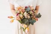 Mladá hezká žena v bílé blůze drží tulipán květiny kytice v rukou proti bílé zdi. Rekreační oslava slavnostní květinový koncept