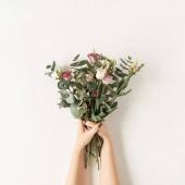 Női kéz kezében színes rózsa virágok csokor ellen fehér fal. Ünnepi ünnepi virágos koncepció