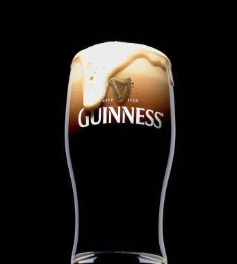 POLTAVA, UKRAINE - MARCH 22, 2018: Glass of Guinness original beer on black background. Guinness beer has been produced since 1759 in Dublin, Ireland.