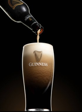 POLTAVA, UKRAINE - MARCH 22, 2018: Guinness beer is pouring into a glass. Guinness beer has been produced since 1759 in Dublin, Ireland