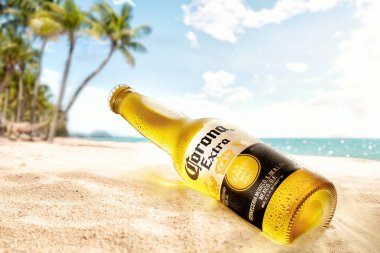 bottle of cold corona extra beer on beach sand