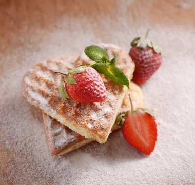 heart-shaped cookies, strawberries, mint and powdered sugar