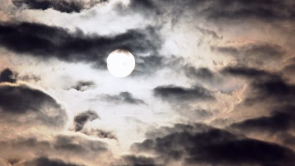 The solar disk is viewed through dark fast-moving clouds.