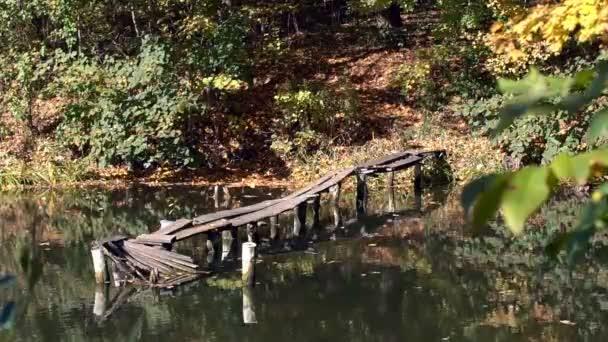 Malý starý most na jezeře. Podzimní krajina jezera v městském parku