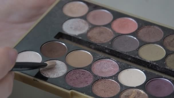 Young woman holding multicolor palette of eyeshadows in hand while make up artist work with her face. Closeup of colourful professional set of eye shadows for beautiful make-up.