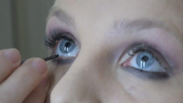 Ta holka dělá pro modré oči profesionální make-up. Pomocí speciálního štětce zakrouží okem černou. To činí oči výraznějším