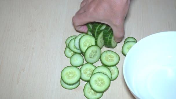 Uborka szeletelés és saláta apróra vágott uborka és saláta aprított zöldségek egy fából készült vágódeszka.