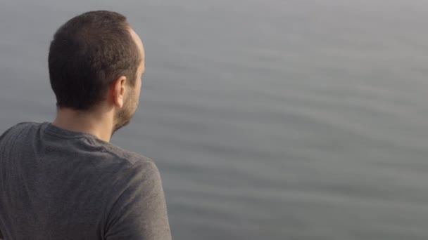 Young Man Sits On The Edge Of The Cliff Looking On The Sea - The Over The Shoulder