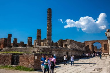 Tourists visiting the Temple of Jupiter at the Forum of the ancient city of Pompeii in a beautiful early spring day