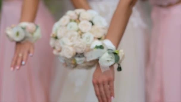 Nevěsta a družičky v růžové šaty drží jejich kytice