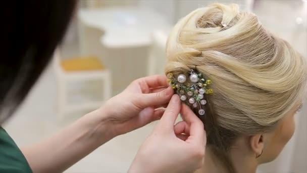 Kadeřník přikládá dekoraci vlasům mladé blonďaté ženy, zblízka