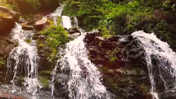 Slow motion of a small mountain waterfall. 240fps. The mountain stream falls down on stones in a bottom.