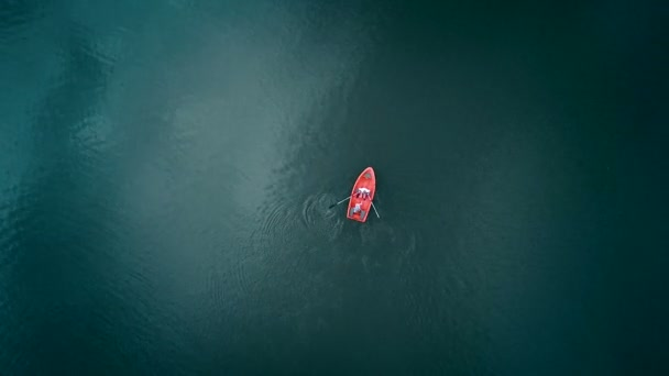 Aerial top view. Red boat on the lake, top view. Two young people are sailing on the boat