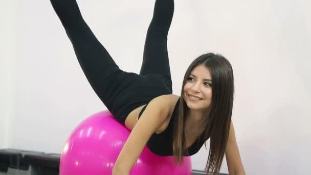 Nettes Mädchen macht Fitnessübungen auf dem Ball. Gesunder Lebensstil im Fitnessstudio