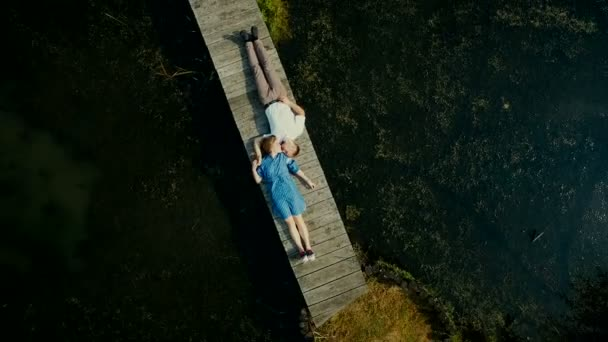 Aerial view on top. Two lovers of young people lie on a wooden bridge. Fairy tale around a young couple. Happy young couple.