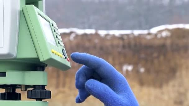 Közelkép ujját, hogy megnyomja a Surveyor gombok a munka a távolság mérésére. A téli építési koncepció
