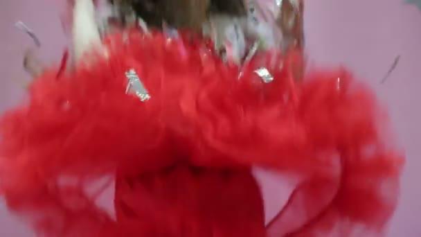 Dívka v červených šatech vyvolá lesklé částice. Party a zábava.