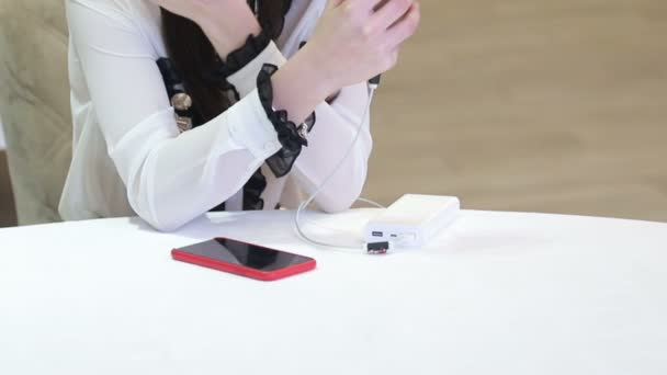 The hands of a girl sitting at a white table hold a cell phone that is charged from a portable charger.