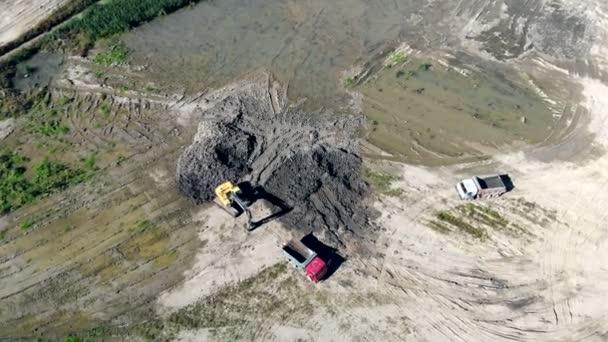 Letecký pohled na přípravu pro nakládku kamionu s vozovkou. Přeprava půdy na staveništi. Vymazání staveniště. Bažina na staveništi