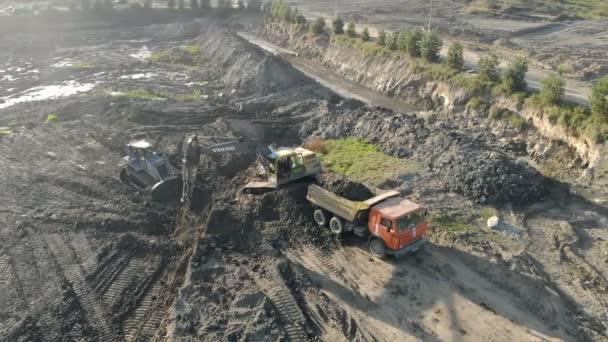 Lvov Ukrajina 29. prosince 2018. Letecký pohled na bagr načte náklaďák s vozovkou. Vymazání staveniště. Bažina na staveništi