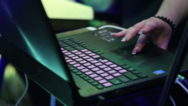 The girls hand makes settings in the laptop during a performance at a party.