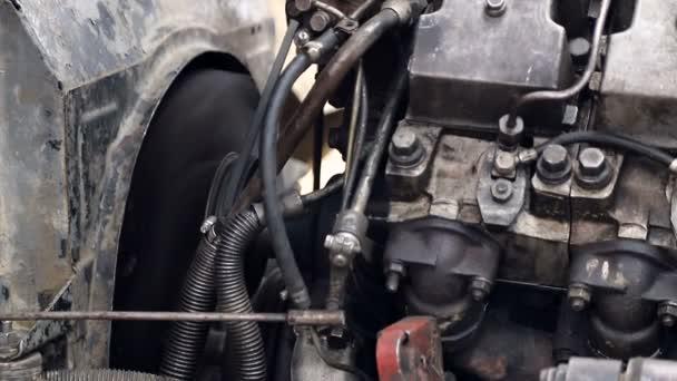 Zaměstnanec opraví buldozer. Opravy těžkých stavebních zařízení na staveništi